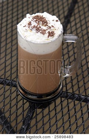Mocha Cappuccino with whipped cream chocolate powder on mesh table outside