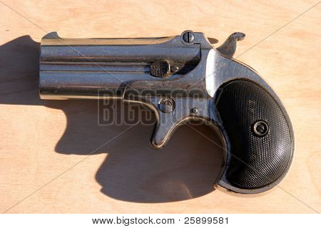 an antique 2 shot .45 cal derringer hand gun
