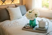 Bedroom Decorative Objects On The Bed In Cozy Vintage Bedroom. Flower Vase, Ceramic Tea Pot, Glass C poster