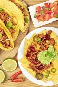 An Overhead Photo Of Mexican Tacos, Pico De Gallo, And Nachos With Chili Con Carne And Guacamole poster