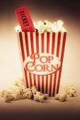 foto of olden days  - Depiction Of The Fifties Cinema Era With A Vintage Red Striped Old Popcorn Box Overflowing With Buttered Popcorn Coupled With A Movie Ticket - JPG