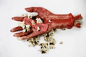 stock photo of gruesome  - Scary Image Of A Bloodied Dismembered Hand Holding Popcorn And Tickets To The Movies In A B - JPG