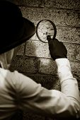 stock photo of crime solving  - Retro Private Eye Detective Searching For Clues By Investigating A Suspected Crime Scene Wall With A Magnifying  - JPG