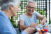 Elderly man wearing spectacles sitting with his wife for breakfast while he shows her a newspaper ar poster