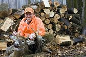 image of hunters  - deer hunter in blaze orange with a ten point whitetail trophy buck with a wood pile in the background - JPG