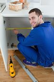 stock photo of formica  - Portrait of a smiling repair man measuring something in a kitchen - JPG