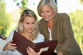 stock photo of memento  - Looking at a family photo album - JPG