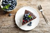 Plate With Chocolate Sponge Berry Cake And Bowl Of Berries On Wooden Background, Top View poster