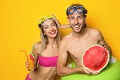 Happy Young Couple In Beachwear With Inflatable Ring And Cocktail On Color Background poster