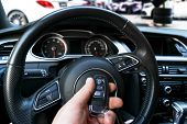 Mans Hand Holding A Wireless Car Key In Black Leather Interior. Modern Car Interior Details. Car De poster