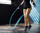 Young Serious Female Boxer In Wrapped Hands Warming Up, Jumping On Skipping Rope In Gym. Fit Woman P poster
