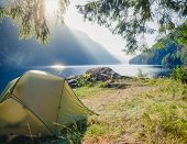 Sunlit camping tent at scenic campsite on a lake shore with mountain range in background - wild camp poster