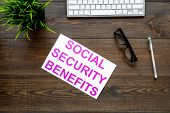 Socail Security. Printed Words Social Security Benefits On Dark Wooden Office Desk Background With C poster