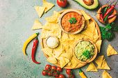 Mexican Nachos With Guacamole, Salsa And Cheese Dip In Wooden Bowls On Dark Background, Top View. De poster