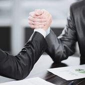 Close Up. Two Businessmen Are Engaged In Arm Wrestling At A Desk poster