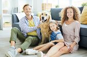 Smiling members of young modern family and their purebred friendly pet relaxing at home poster