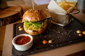 Closeup Of Fresh Burger With Basket Of French Fries On Stone Table With Bowl Of Tomato Sauce.tasty,  poster