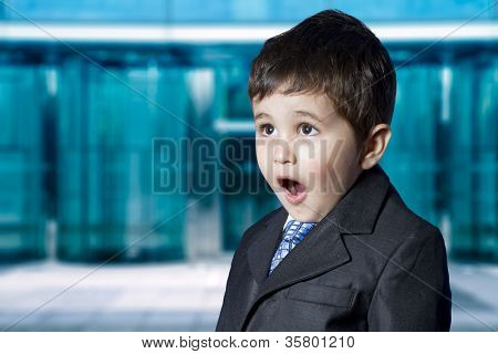 Stock Market. Surprised businessman child in suit with funny face