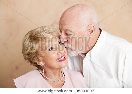 Senior man gives his beautiful wife a kiss on the cheek.
