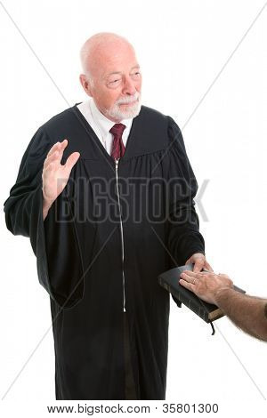 Judge swearing in a witness on the Holy Bible.  Isolated on white.