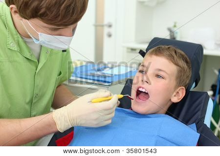 Young dentist looks at teeth of little boy in dental clinic. Focus on patient.