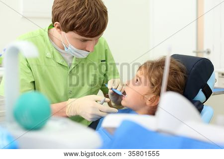 Young dentist looks at teeth of little girl in dental clinic. Focus on doctor.