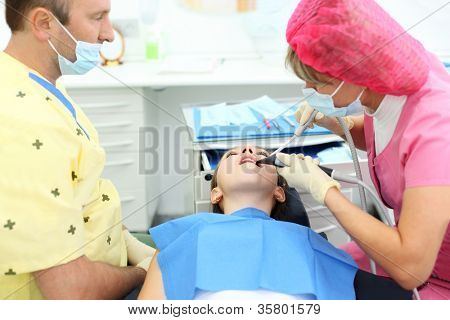 Dentist and assistant treated teeth to girl sitting in chair in dental clinic. Focus on patient. Shallow depth of field.