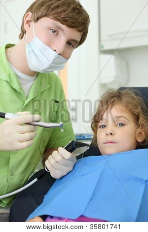 Young dentist holds saliva suction and grinding drill and patient girl lies in chair in dental clinic.