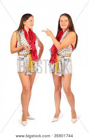 Two same women in studio on white background. First woman smiles and second woman points at double.