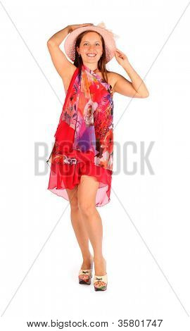 Happy woman dressed in bright pareo and hat poses in studio on white background.