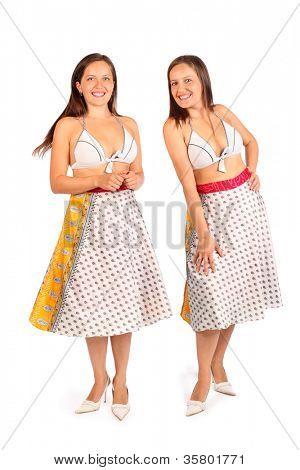 Two same women dressed in bikini and skirt smiles in studio on white background.