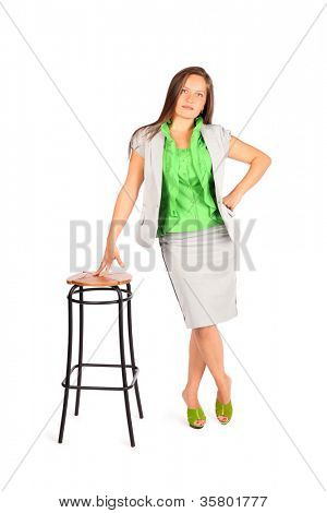 Young beautiful business woman stands leaning on tall stool in studio on white background.