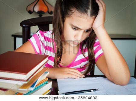 Colegiala enojado y cansado con una pila de libros en su escritorio