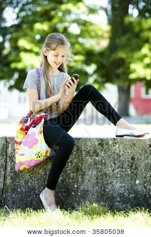 Little girl sending text messaging with mobile phone while sitting outdoors