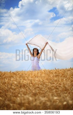 Young woman with white scarf on wind standing in wheat field