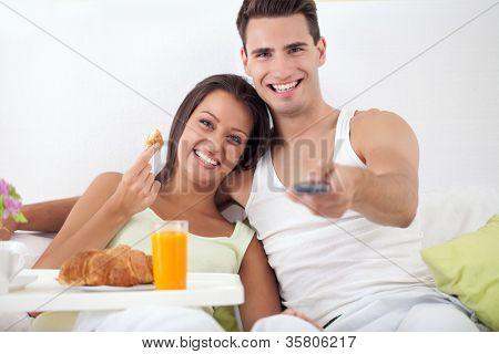 Smiling young couple spending free time together in bed