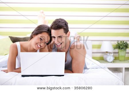 Couple enjoying using laptop in bed for the internet