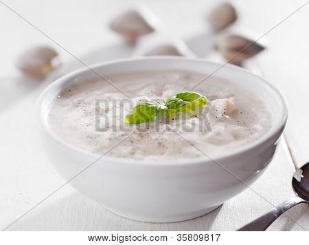 Bowl of new england clam chowder with basil garnish.