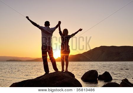 Guy with Girl raised her hands to the sky and watching the sun