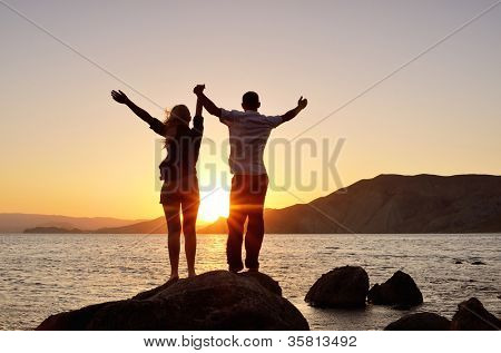 Young couple watching the sun, raising his hands to the sky