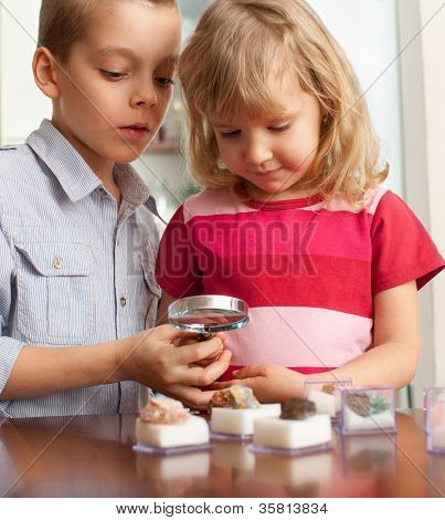 Children are considering a magnifying glass collection of stones