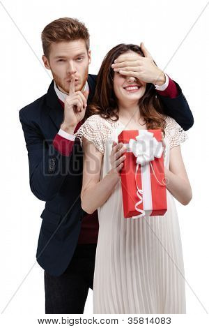 Making silence gesture man closes eyes of his girlfriend to give a present, isolated on white