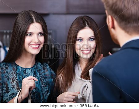 Two young women smiles at shop assistant