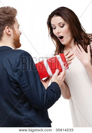 Man surprises his girlfriend with present wrapped in red paper, isolated on white