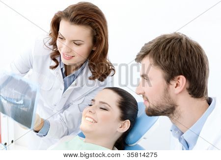 The patient thoroughly examines the x ray photo of her teeth. She is happy that everything is ok