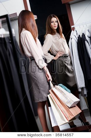 Woman admires herself at the mirror in the store while handing packets with purchases