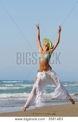 Woman Standing On Shoreline At The Beach In Greece