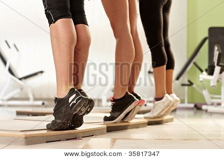 Muscular female calves exercising at the gym.