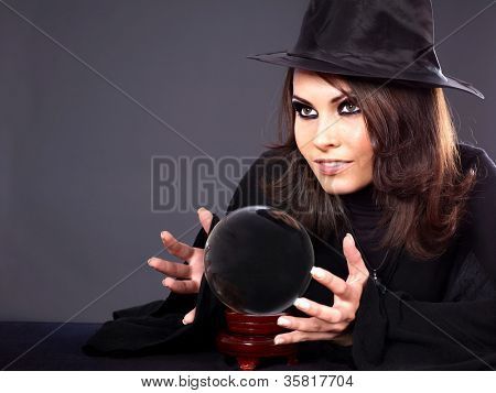 Woman wearing witch hat with crystal ball. Fortune telling.