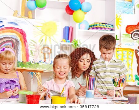 Child with teacher painting  in art school.